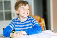 Happy school kid boy at home making homework Stock Images