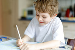 Happy school kid boy at home making homework Royalty Free Stock Image