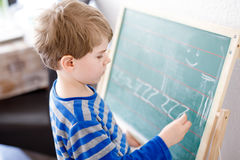 Happy school kid boy at home making homework Royalty Free Stock Images