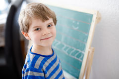 Happy school kid boy at home making homework Stock Photography