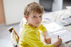 Happy school kid boy at home making homework. Portrait of cute school kid boy at home making homework. Little concentrated child writing with colorful pencils Stock Photo