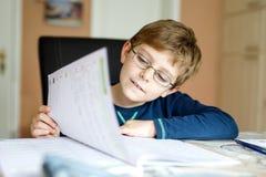 Happy school kid boy at home making homework. Portrait of cute school kid boy wearing glasses at home making homework. Little concentrated child writing with Stock Photo