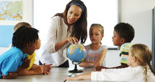 Happy school kids with globe in classroom stock video footage