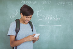 Happy schoolboy with backpack using mobile phone in classroom Stock Photos