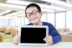 Happy schoolboy with empty tablet screen. Joyful little boy sitting in the classroom while showing empty tablet screen and smiling at the camera Stock Photography