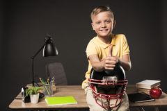 happy schoolboy holding american football helmet doing thumb up gesture and sitting on table with books plant lamp colour