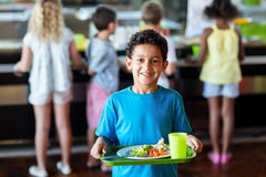 Happy schoolboy holding food tray in canteen. Portrait of happy schoolboy holding food tray in canteen against classmates stock photo