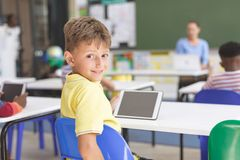 Happy schoolboy looking at the camera and holding a digital tablet at desk in classroom. Rear view of a happy schoolboy looking at the camera and holding a stock photos