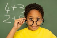 Happy schoolboy looking over spectacle against greenboard in a classroom. Rear view of happy mixed-race schoolboy looking over spectacle against greenboard in a stock image