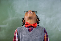 Happy schoolboy looking up and laughing in classroom Stock Images