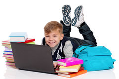 Happy schoolboy lying on floor with laptop Royalty Free Stock Photos