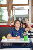 Happy Schoolboy Raising Hand In Classroom. Portrait of happy schoolboy raising hand while studying at desk in classroom Royalty Free Stock Photography