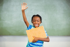 Happy schoolboy raising his hand and holding books in class room Royalty Free Stock Photography
