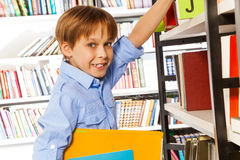 Happy schoolboy searching books in library Stock Photos
