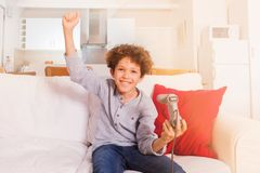 Happy boy holding game controller of videogame. Happy schoolboy sitting on the coach and holding game controller of videogame, celebrating win with his hands up Royalty Free Stock Image