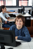 Happy Schoolboy Sitting With Computer At Desk Stock Images