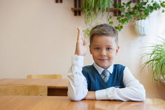 Happy schoolboy sitting at desk Royalty Free Stock Images