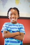Happy schoolboy standing with arms crossed in classroom Royalty Free Stock Photos