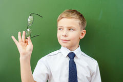 Happy schoolboy standing near the blackboard with medical glasses Stock Photography