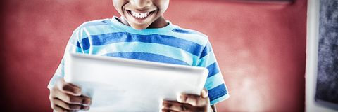 Schoolboy using digital tablet in classroom royalty free stock photo