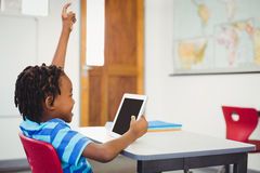 Happy schoolboy using digital tablet in classroom. Happy schoolboy sitting on chair and using digital tablet in classroom at school Stock Photography