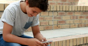 Happy schoolboy using mobile phone stock footage