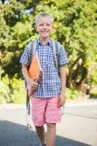Happy schoolboy walking in campus. Portrait of happy schoolboy holding book and walking in campus Royalty Free Stock Photos