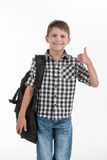 Happy schoolboy wearing backpack and giving thumbs up. Royalty Free Stock Image