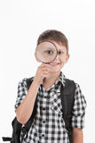 Happy schoolboy wearing backpack and holding magnifying lens. Stock Image