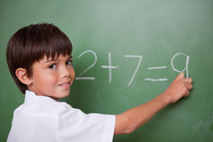 Happy schoolboy writing an addition Royalty Free Stock Images