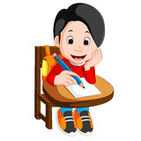 Happy schoolboy writing in class Royalty Free Stock Images