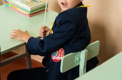 Happy schoolboys sitting at desk, classroom royalty free stock photography