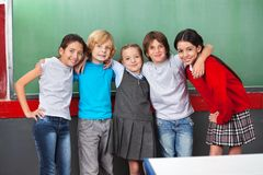 Happy Schoolchildren With Arms Around Standing Stock Images
