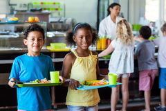 Happy schoolchildren holding food tray in canteen. Portrait of happy schoolchildren holding food tray in canteen against classmates stock photo