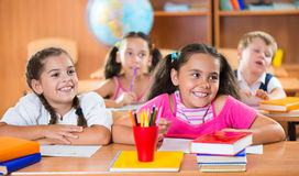 Happy schoolchildren during lesson in classroom Stock Images