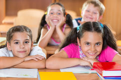 Happy schoolchildren during lesson in classroom Stock Photos