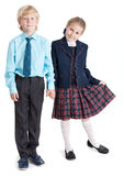 Happy schoolchildren in school uniform standing together holding hands, full length, isolated white background Royalty Free Stock Image