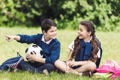 Happy schoolchildren sitting on grass in park with backpacks and soccer ball. And chatting stock image