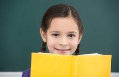 Happy schoolgirl.  Cheerful little schoolgirl looking out from t Stock Photos