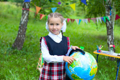 Happy schoolgirl child kid girl holding globe and smiling, point Royalty Free Stock Image