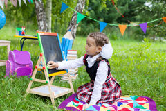 Happy schoolgirl child kid girl sitting on grass and writing on Stock Photography