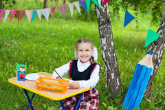 Happy schoolgirl child kid girl sitting at table and writing, cl Royalty Free Stock Photography