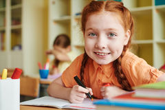 Happy schoolgirl. Cute pupil drawing with highlighter and looking at camera Royalty Free Stock Images