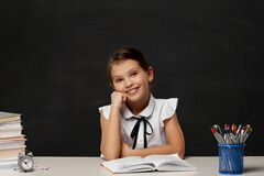 Free Happy Schoolgirl Daydreaming And Sitting At Table Stock Images - 217694654