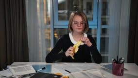A happy schoolgirl is eating a banana. Lunch break. She`s doing her homework. stock video