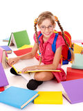 Happy schoolgirl in eyeglasses with pile of books. Happy sitting schoolgirl in eyeglasses  with  pile of books. Isolated Royalty Free Stock Photos