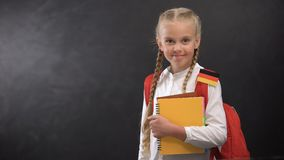 Happy schoolgirl holding books with German flag, ready to learn foreign language. Stock footage stock video