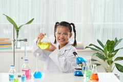 Girl with chemical reagent. Happy schoolgirl holding flask with yellow reagent Stock Image