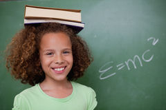Happy schoolgirl holding her book on her head Royalty Free Stock Photos