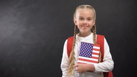 Happy schoolgirl holding textbook with printed USA flag against blackboard. Stock footage stock video footage